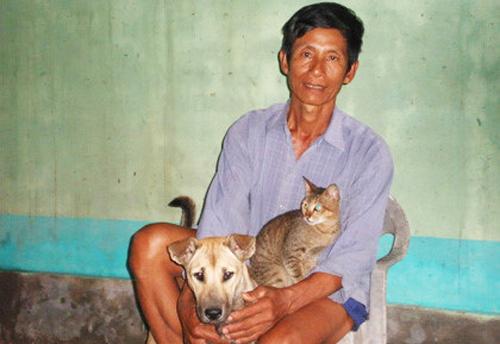 Tư Trạng bên con mèo rừng và chú chó săn sau hơn chục năm bỏ nghề. Ảnh: Hoàng Hạnh.