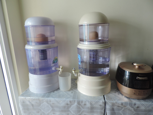 Anh Nguyễn Hữu Vinh dùng hai bình lọc để xử lý nguồn nước sinh hoạt để nấu ăn.