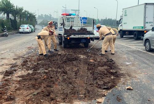 Tổ công tác của đội csgt số 15 huy động xe chuyên dụng để dọn đống đất đổ giữa đường Võ Văn Kiệt.Ảnh: Sơn Dương